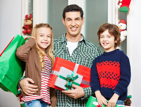 Happy father with two children and gifts at christmas eve photo