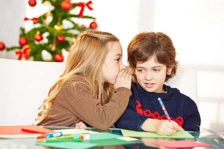 wishlist: Girl whispering a wish in the ear of a boy at christmas
