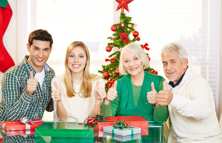 Couple and senior people holding thumbs up at christmas with gifts photo