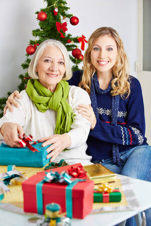Happy woman with smiling senior mother and gift for christmas Stock Photo