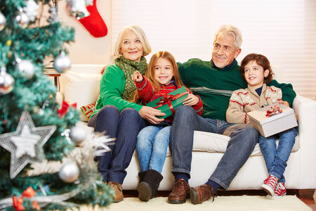 Grandparents celebrating christmas with their two grandchildren and gifts photo