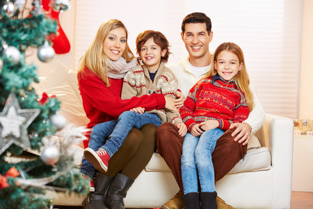 Happy family and children celebrating christmas with a christmas tree photo