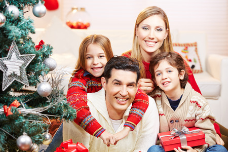 Happy family with two kids at christmas with gifts photo