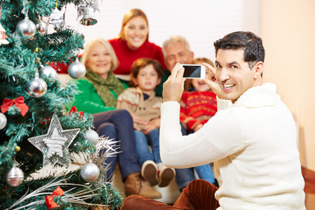 Smiling man taking family picture at christmas with his smartphone camera photo