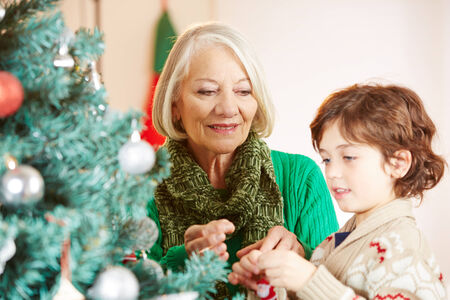grandmother grandchild: Grandchild and grandmother decorating together the christmas tree