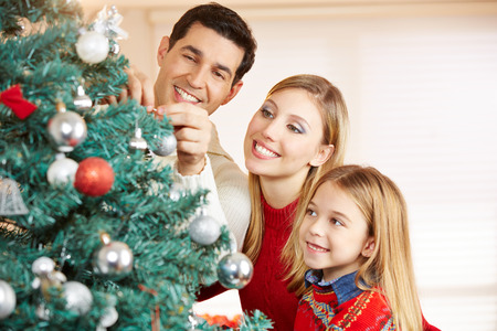 decorating christmas tree: Happy family decorating christmas tree together at home Stock Photo