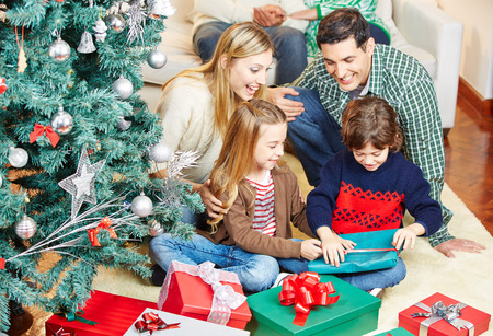 Happy Children Opening Gifts At Christmas While Parents And ...