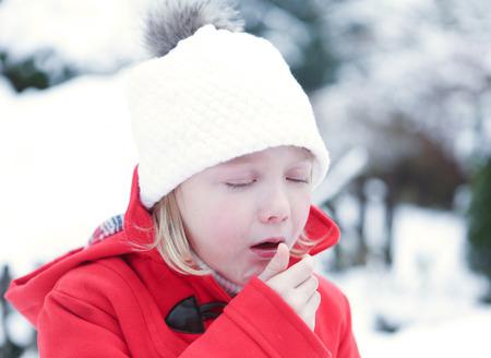 tosiendo: Muchacha enferma con la gripe tose en un invierno cubierto de nieve Foto de archivo