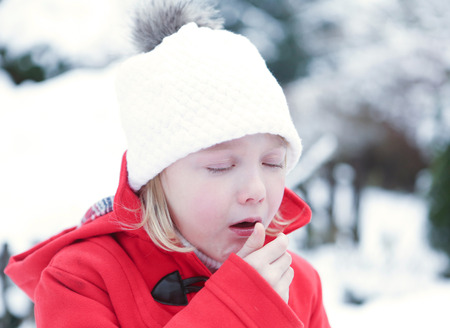 coughing: Sick girl coughing with flu in a snowy winter