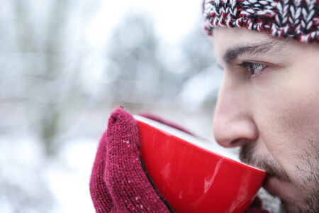 hot soup: Man drinking hot tea in winter from a red cup