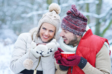 forest tea: Happy couple laughing together with hot tea in winter Stock Photo