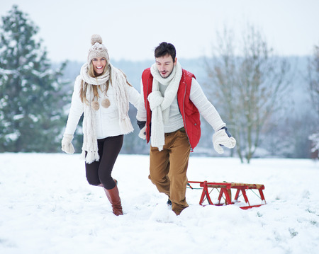Happy couple pulling sled in winter up a snowy hill photo