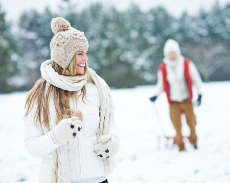 Happy woman running through winter snow and man pulling a sled