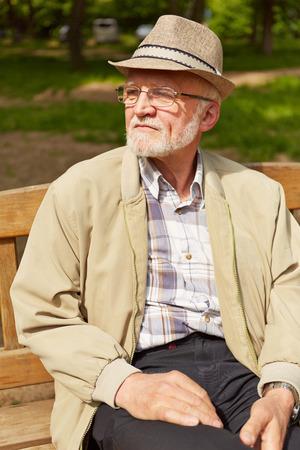 banc de parc: Vieil homme au chapeau et des lunettes assis sur un banc de parc en été