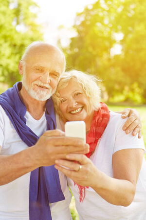 Happy senior couple taking a selfie with smartphone in a fall garden photo