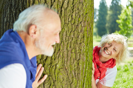 hide and seek: Happy senior couple playing hide and seek together in nature