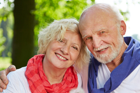 Old man and woman as senior couple in nature in fall photo