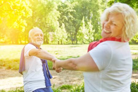 Glückliche ältere Paare tanzen in einem Garten im sonnigen Sommertag
