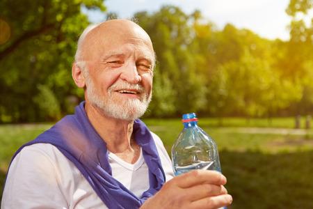 Thirsty senior man drinking fresh water after sports Foto de archivo