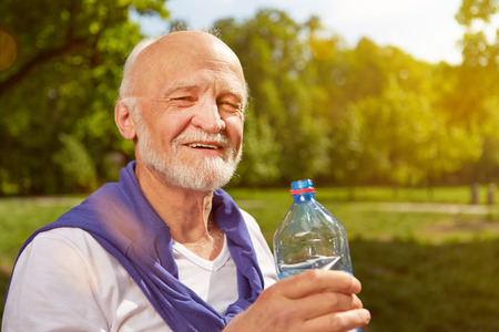old man: Thirsty senior man drinking fresh water after sports Stock Photo