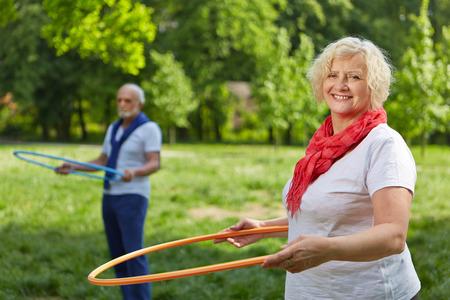 fitness training: Twee lachende senior mensen doet fitness training in een zomertuin