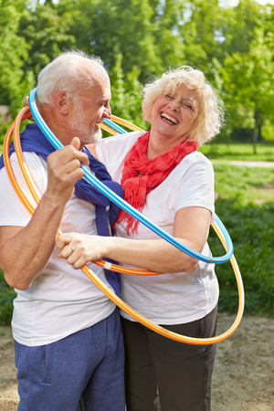 vital: Happy senior couple together in a hoop in summer Stock Photo