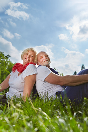 Happy senior couple sitting on a meadow in summer photo
