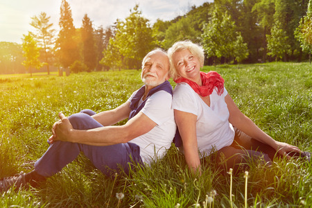 Happy senior couple sitting in summer vacation on a green meadow photo