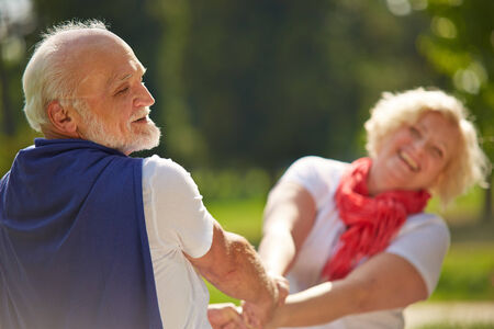 Old senior couple dancing happy together in nature photo