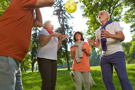 ancianos felices: Feliz grupo de personas mayores que juegan con una pelota en un parque