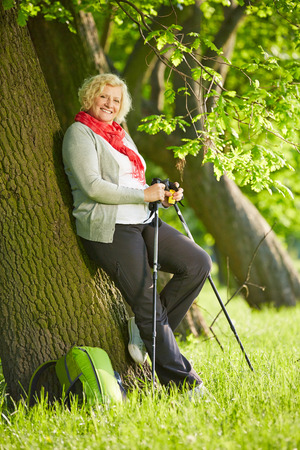 Happy senior woman with hiking sticks leaning on a tree photo
