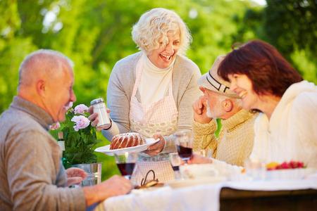 persona de la tercera edad: Feliz grupo de gente mayor que come la torta anillo en la fiesta de cumplea�os en un jard�n