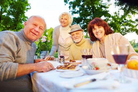 eten: Gelukkig senior mensen zitten op gezette koffie tafel in een zomertuin