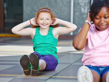 elementary school: Girls doing sit-ups in physical education in elementary school
