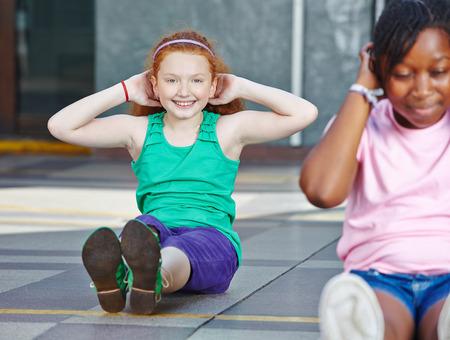 educacion fisica: Ni�as haciendo abdominales en la educaci�n f�sica en la escuela primaria