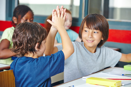 Two happy elementary school students giving high five in class