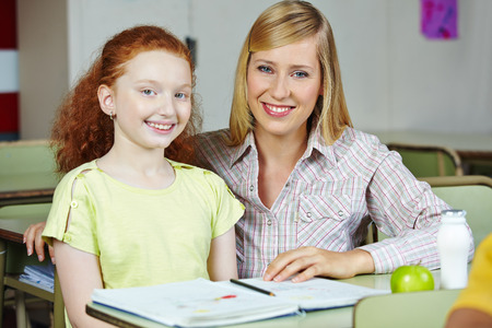 private schools: Happy teacher giving smiling girl private lessons after school