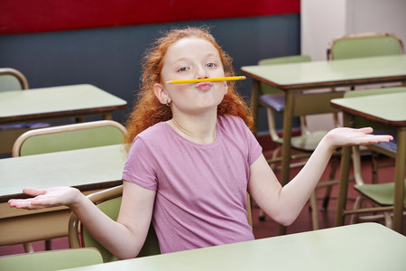 nonsense: Girl doing nonsense in elementary school class with a pencil over her lips