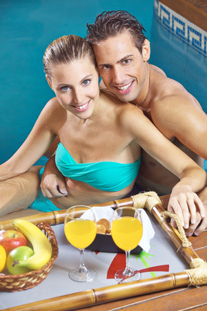 Happy couple having breakfast in swimming pool photo