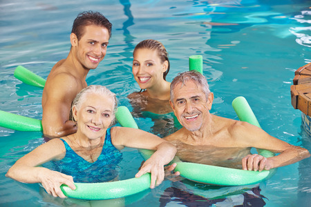 Group with couple and senior citizens having fun in a swimming pool