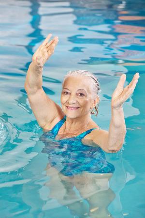 Senior vrouw tillen haar armen in aquafitness klasse in een zwembad Stockfoto