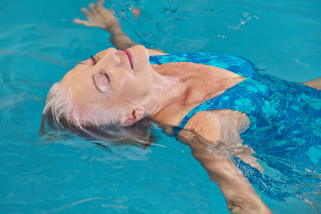 senior old: Happy senior woman relaxing in swimming pool with water yoga