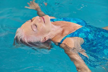nadar: Mujer mayor feliz que se relaja en la piscina con agua de yoga