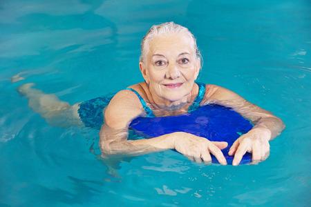Vieja mujer nadando en el agua con una tabla flotadora en una piscina del hotel