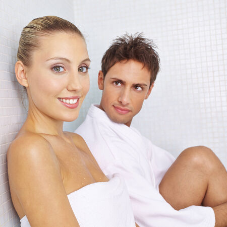 heated: Smiling couple resting in relaxation room in spa after sauna session