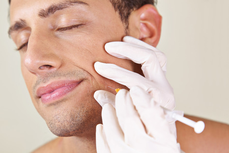 attractiveness: Man in a beauty clinic getting wrinkle treatment near his mouth
