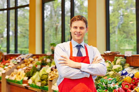 Portrait of supermarket store manager in front of fresh vegetables photo