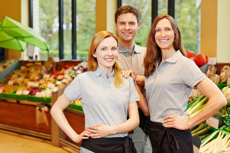 merchant: Happy team in supermarket with store manager and two salespeople Stock Photo