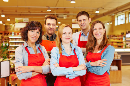 salespeople: Team of five happy salespeople together in a supermarket with their arms crossed