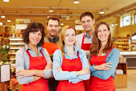 Team von fünf glücklich Verkäufer zusammen in einem Supermarkt mit ihren Armen gekreuzt Standard-Bild